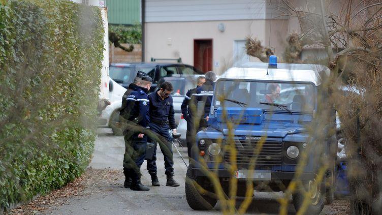 Des gendarmes perquisitionnent une maison à Talloires (Haute-Savoie) le 18 février 2014 après l'arrestation d'un suspect dans l'enquête sur la tuerie de Chevaline. (JEAN-PIERRE CLATOT / AFP)