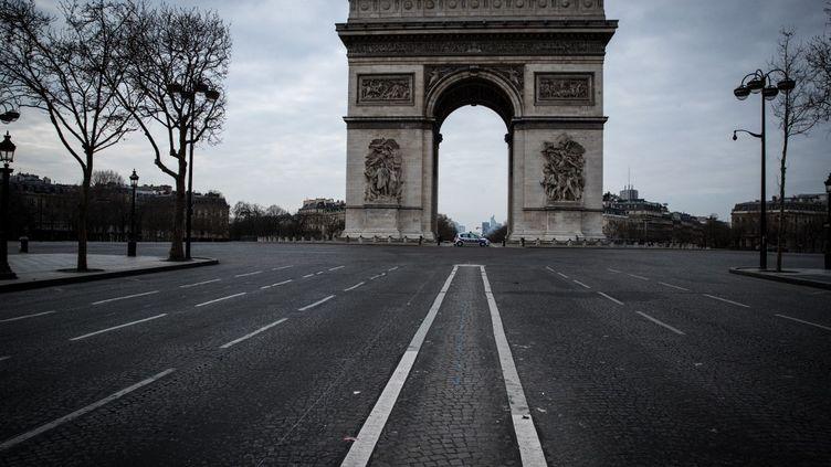 Le rond-point de l'Arc de Triomphe vide, lors du premier confinement le 17 mars 2020. (JOEL SAGET / AFP)