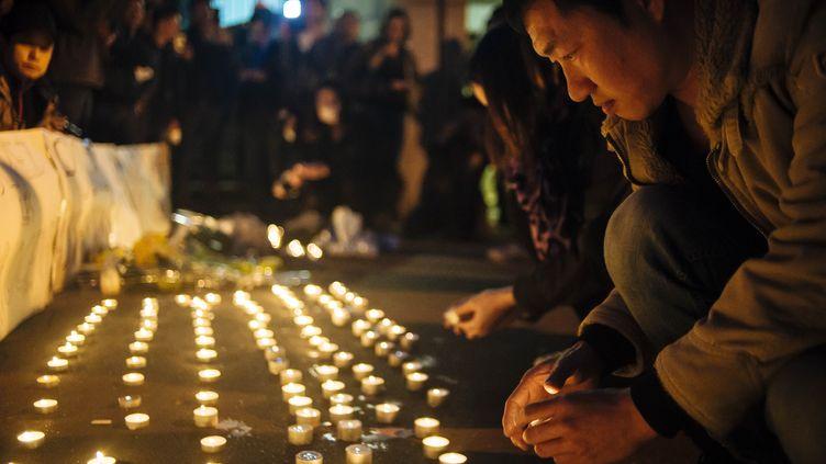 Un homme se recueille en mémoire de Liu Shaoyao, mardi 28 mars 2017, devant le commissariat du 19e arrondissement de Paris. (JAN SCHMIDT-WHITLEY / NURPHOTO / AFP)