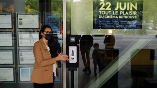 Natacha Bouchaudon, directrice de l'UGC Paris 19, se nettoye les mains avec un distributeur de gel hydroalcoolique disposé dans le cinéma. (THOMAS COEX / AFP)