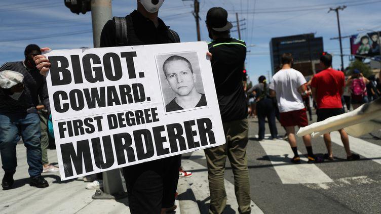Un manifestant tient une pancarte avec une photo de l'ancien policier de Minneapolis Derek Chauvin lors des rassemblements qui ont suivi la mort de George Floyd le 30 mai 2020, à Los Angeles (Californie), aux Etats-Unis. (MARIO TAMA / GETTY IMAGES NORTH AMERICA)