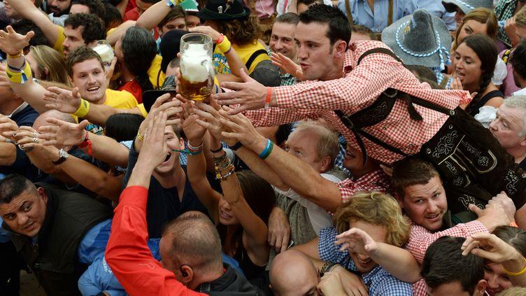 Des festivaliers tentent d'attraper la première bière servie lors de l'ouverture de l'Oktoberfest, à Munich (Bavière, Allemagne), le 21 septembre 2013. (CHRISTOF STACHE / AFP)