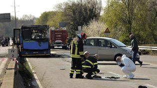 Les enquêteurs examinent les restes calciné du bus, mercredi 20 mars à San Donato (Italie). (FLAVIO LO SCALZO / AFP)