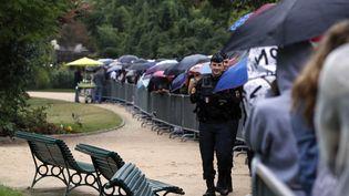 Un policier patrouille le long de la file d'attente pour la visite du palais de l'Elysée à l'occasion des Journées du patrimoine le 17 septembre 2016 à Paris. (FRANCOIS GUILLOT / AFP)