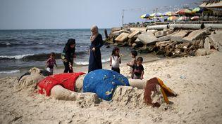Des Palestiniennes déposent des fleurs, lundi 7 septembre 2015 à Gaza, sur une statue de sable représentant Aylan, le jeune réfugié mort en mer en fuyant la Syrie. (MOHAMMED ABED / AFP)