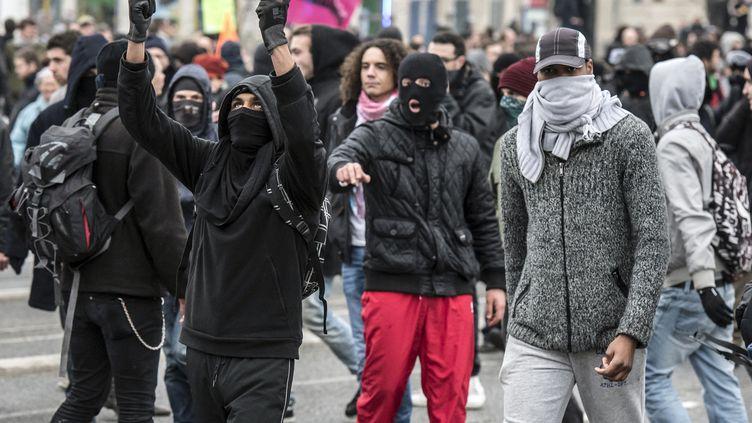 Des manifestants cagoulés ont brisé des vitrines de commerces à Lyon, samedi 29 novembre, lors d'une manifestation contre le congrès du FN dans la ville. (JEAN-PHILIPPE KSIAZEK / AFP)