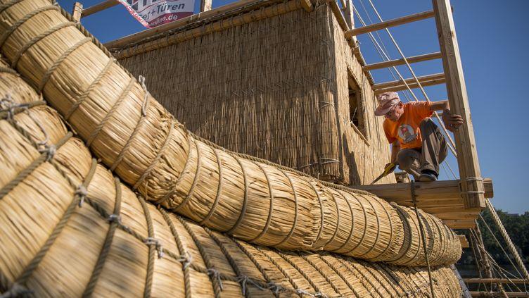 L'assemblage d'une embarcation de 14 mètres de long en roseau qui va tenter la traversée de la Méditerranée (Beloslav, Bulgarie, 26 juillet 2019) (NIKOLAY DOYCHINOV / AFP)