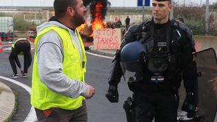 """Un gendarme et un manifestant """"gilet jaune"""" près du dépôt de pétrole dePort-La-Nouvelle (Aude), le 20 novembre 2018. (RAYMOND ROIG / AFP)"""