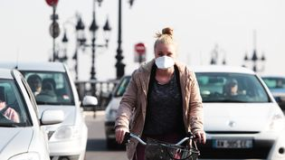 Une jeune femme portant un masque lors d'un pic de pollution à Bordeaux, le 14 mars 2014 (photo d'illustration). (BONNAUD GUILLAUME / MAXPPP)