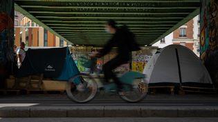 Un cycliste passe devant des tentes, le 3 juin 2020 à Paris. (ANTOINE DE RAIGNIAC / HANS LUCAS / AFP)