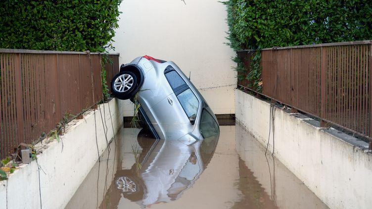 Une voiture renversée dans une allée, le 4 octobre 2015, à Mandelieu-la-Napoule (Alpes-Maritimes). (BORIS HORVAT / AFP)