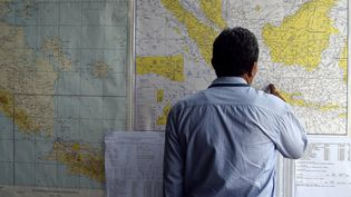 Un homme regarde une carte de la zone de recherches du vol QZ8501 d'AirAsia, disparu le 28 décembre 2014 lors de son trajet entre l'Indonésie et Singapour. (MANAN VATSYAYANA / AFP)