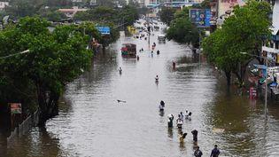Des personnestraversentune rue inondée à la suite d'une forte pluie de mousson, à Bombay (Inde), le 16 juillet 2021. (INDRANIL MUKHERJEE / AFP)