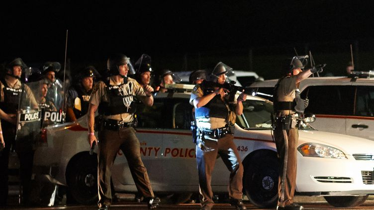Des policiers interviennent à Ferguson (Missouri, Etats-Unis), après des débordements à l'issue d'une manifestation à la mémoire de Michael Brown, le 9 août 2015. (MICHAEL B. THOMAS / AFP)