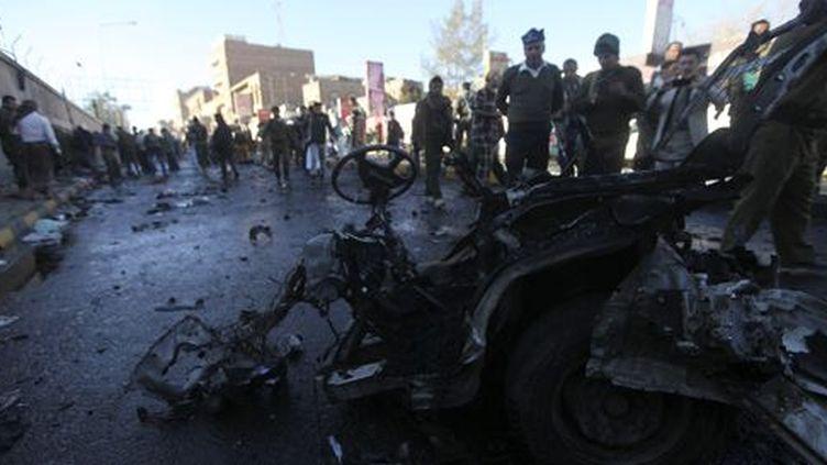 Des policiers observent les restes d'une voiture sur le site de l'attentat qui s'est produit devant l'académie de police à Sanaa le 7 janvier 2015.
