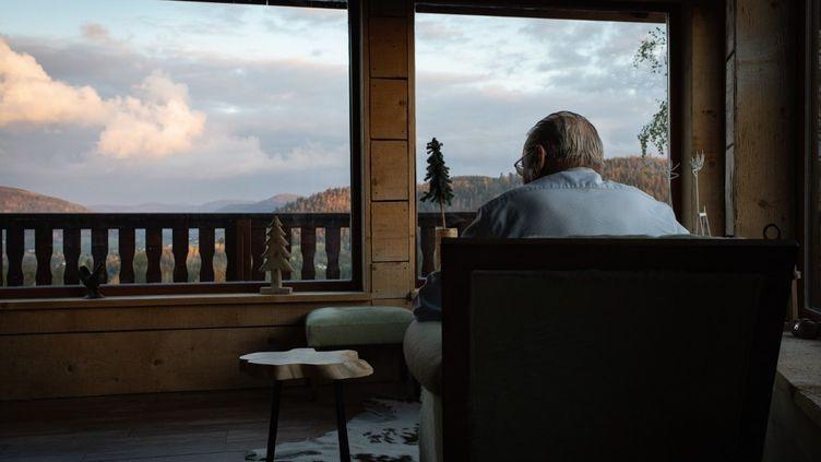 Assis dans son fauteuil, un monsieur regarde par la fenêtre, le 18 octobre 2020, au Tholy (Vosges). (LEO PIERRE / HANS LUCAS / AFP)