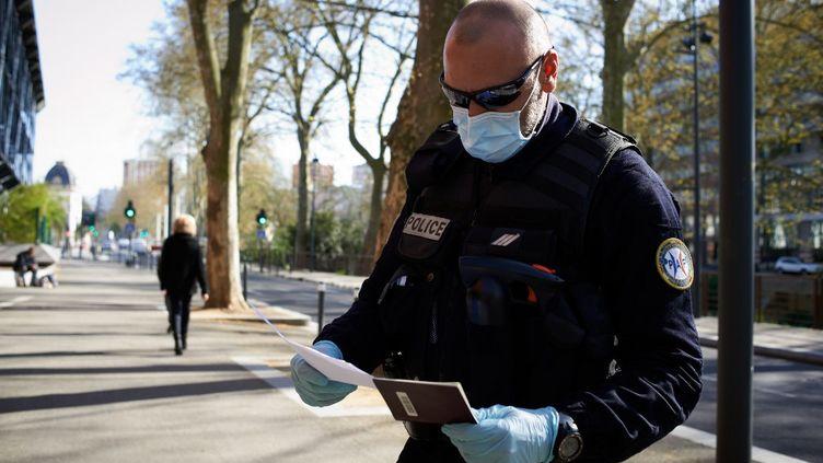 Un policier vérifie l'attestation et le passeport d'un citoyen dans les rues de Toulouse (Haute-Garonne), le 27 mars 2020. (ALAIN PITTON / AFP)