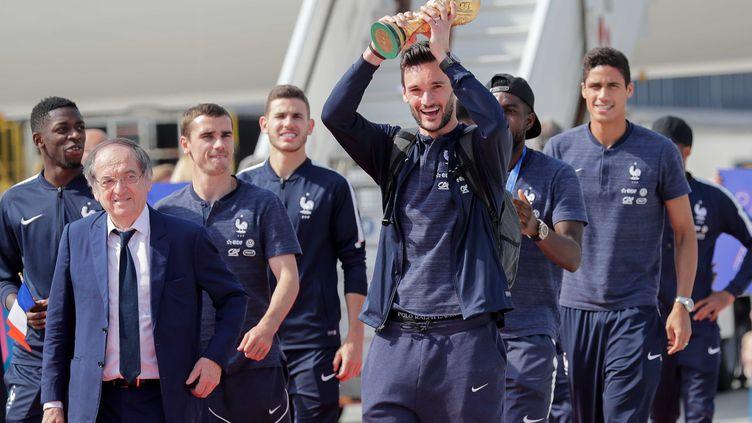 L'arrivée des Bleus à Roissy. Accompagné par ses coéquipiers et par le président de la Fédération Noël le Graët, le capitaine Hugo lloris brandi la Coupe du monde. (THOMAS SAMSON / AFP)