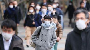 Des passants japonais, dans une rue de Tokyo, mercredi 26 février 2020. (KAZUKI WAKASUGI / YOMIURI / AFP)
