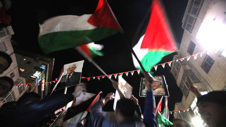 Des Palestiniens célèbrent la décision de l'ONU d'accorder à la Palestine le statut d'Etat observateur, le 29 novembre 2012. (ABBAS MOMANI / AFP)