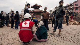 Des sauveteurs de la Croix Rouge aident des blessés à Katmandou (Népal), samedi 25 avril. (CARL WHETHAM / DPA / AFP)