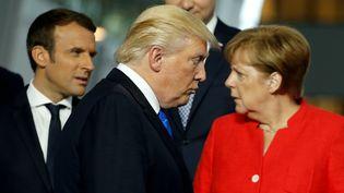 Le president américain Donald Trump passe devant son homologue français Emmanuel Macron et la chancelière allemande Angela Merkel, le 25 mai 2017 à Bruxelles. (JONATHAN ERNST / REUTERS)
