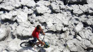 Un homme se déplace à vélo sur la glace, le 30 juin 2019 à Guadalajara (Mexique). (ULISES RUIZ / AFP)