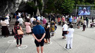 Des pélerins assistent à la retransmission d'une messe du pape François sur un écran, le 30 mai 2020 à Lourdes (Hautes-Pyrénées). (LAURENT DARD / AFP)