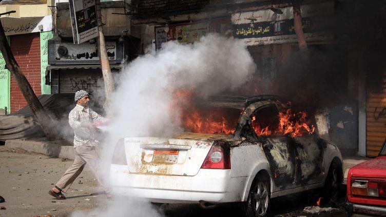 Une voiture flambe dans une rue du Caire, en Egypte, le 25 janvier 2014. (AHMED TARANH / ANADOLU AGENCY / AFP)