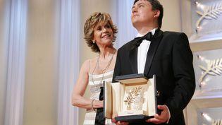 Le réalisateur roumain, Cristian Mungiu, soulève la palme d'or, aux côtés de Jane Fonda, au festival de Cannes 2007. (TONY BARSON ARCHIVE / WIREIMAGE)