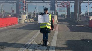 """Pendant ce temps, la mobilisation continue ailleurs en France. Comme ici, à Muret près de Toulouse (Haute-Garonne), à l'entrée d'un péage, où l'on retrouve une femme arborant un gilet jaune qui brandit une pancarte sur laquelle est écrit : """"Souriez, c'est pas taxé"""". (PASCAL PAVANI / AFP)"""