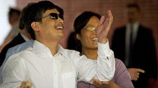 Le dissident chinoisChen Guangcheng et sa femmeYuan Weijing saluent les journalistes à leur arrivée à New York (Etats-Unis), le 19 mai 2012. (MLADEN ANTONOV / AFP)