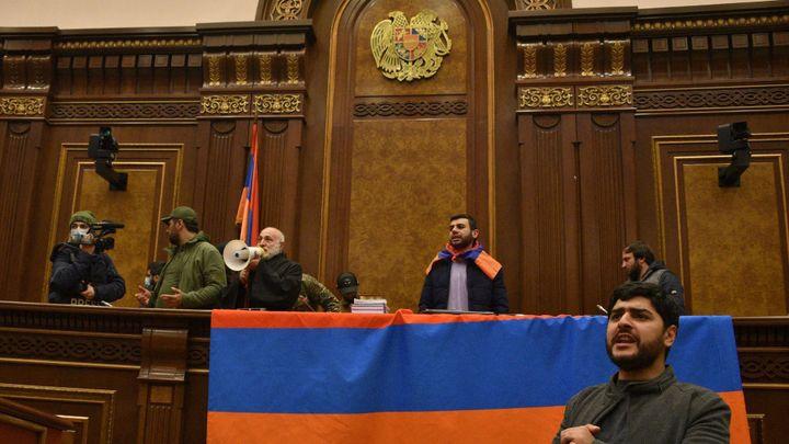 Des manifestants arméniens à la tribune du Parlement à Erevan, le 10novembre. (KARENMINASYAN / AFP)