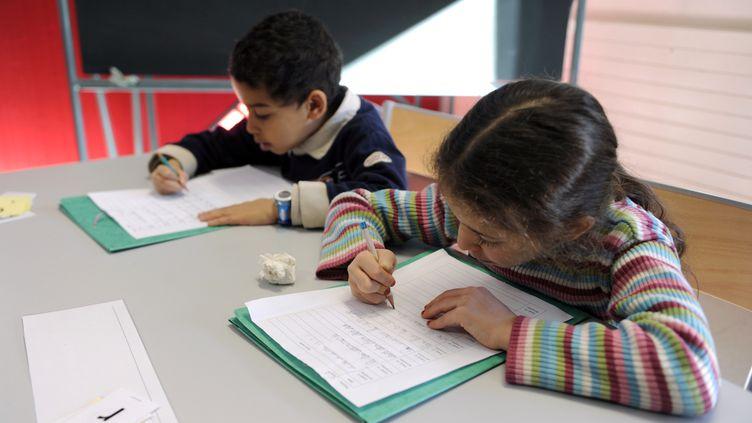 Des écoliers en CP passent une évaluation. (Illustration). (PHILIPPE DESMAZES / AFP)