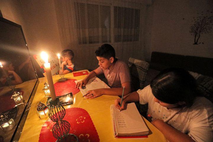 Lorsque les générateurs sont enfin coupés, il ne reste plus parfois que les bougies pour s'éclairer, comme dans cette famille de Tripoli le 26 août 2021. (MAHMUD TURKIA / AFP)