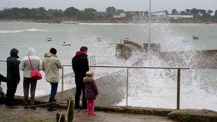 Des promeneurs observent les vagues frapper la côte à Ploermeur (Morbihan), le 3 janvier 2016. (JEAN-SEBASTIEN EVRARD / AFP)