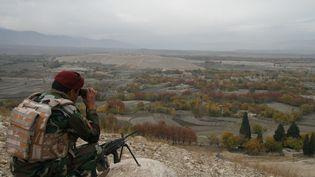 Un soldat de l'armée afghane surveille une zone d'où 9 000 familles ont fui à cause des combats entre l'Etat islamique et les talibans, le 28 novembre 2017, à Hogyani (Afghanistan). (ZABIHULLAH GHAZI / AFP)