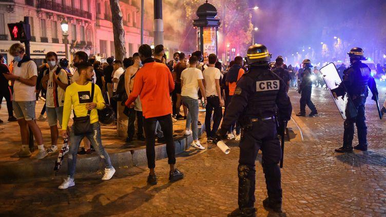 Des CRS encadrent des supporters qui célèbrent la qualification du PSG en finale de la Ligue des champions, le 18 août 2020 (JULIEN MATTIA / ANADOLU AGENCY)