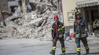 Des pompiers marchent au milieu des bâtiments détruits par le séisme à Amatrice, en Italie, le 30 août 2016. (MANUEL ROMANO / NURPHOTO / AFP)