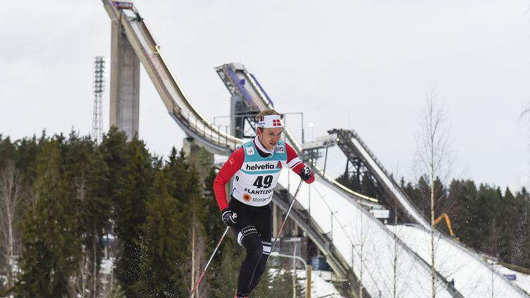 Le Danois Jens Hulgaard passe devant les deux tremplins de Lahti (Finlande) lors des qualifications pour le 10 km individuel hommes, le 22 février (JONATHAN NACKSTRAND / AFP)