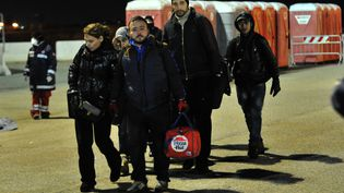 Des migrants descendent de l'Ezadeen, le cargo abandonné, arrivé au port italien de Corigliano, le 2 janvier 2015. (ALFONSO DI VINCENZO / AFP)