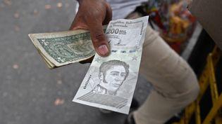 Un homme montre un nouveau billet de bolivar, à Caracas, le 14 avril 2021. (FEDERICO PARRA / AFP)