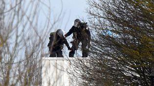 Deux policiers prennent position sur le toit de l'imprimerie de Dammartin-en-Goële (Seine-et-Marne), le 9 janvier 2015. (DOMINIQUE FAGET / AFP)