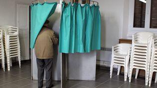 Un électeur dans l'isoloir à Frasseto (Corse-du-Sud), lors du premier tour des élections départementales, le 22 mars 2015. (PASCAL POCHARD-CASABIANCA / AFP)
