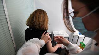 Une soignante vaccine une patiente, le 25 février 2021, à Paris. (ALAIN JOCARD / AFP)