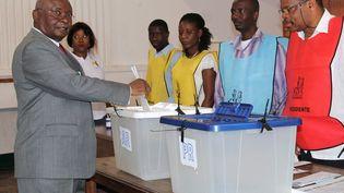 L'ancien président du Mozambique, Armando Guebuza (à gauche), déposant son bulletin dans l'urne lors des élections générales du 15 octobre 2014, à Maputo. (JORGE TOME / AFP)