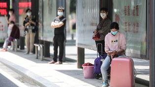 Des voyageurs attendent à une station de bus de la ville chinoise de Wuhan, d'où est partie l'épidémie de Covid-19, le 11 mai 2020. (AFP)
