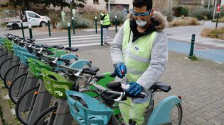 Un salarié désinfecte des Velib' à Suresnes (Hauts-de-Seine). Photo d'illustration. (THOMAS SAMSON / AFP)