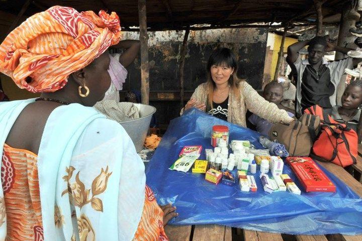 Une Chinoise en train de vendre des produits médicinaux sur le marché de Kamsar, au nord de Conakry, capitale de la Guinée. (GEORGES GOBET / AFP)