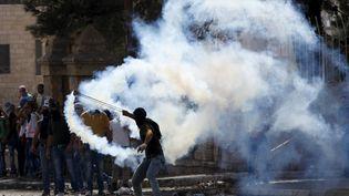 Un Palestinien renvoit une grenade lacrymogène envoyée par les forces israéliennes, le 14 octobre 2015 à Bethléem (Territoires palestiniens). (MUSSA QAWASMA / REUTERS)